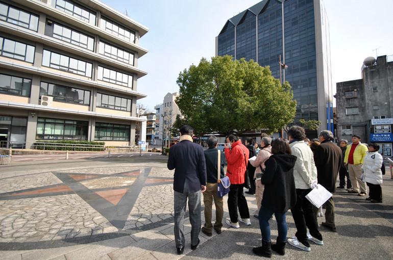 長崎市役所広場にて、市役所の現地建替えが可能なことについて説明に聞き入る参加者の皆さん。